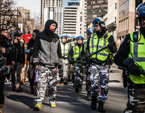 Policeman and Protester looking each other in the eyes and wear Stock Photography