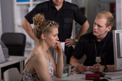 Policeman questioning woman. Young policeman questioning women at police station Royalty Free Stock Photo