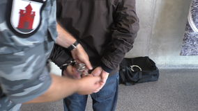 Policeman removing handcuffs from a suspect. Armed police officer or policeman in camouflage uniform unlocking handcuffs and releasing suspect handcuffed thief stock footage