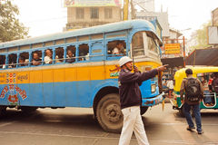 Policeman of road service trying to direct traffic on a street with busses and walking people. KOLKATA, INDIA - JAN 15: Policeman of road service trying to Stock Image