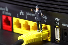Policeman router A. Miniature model policeman standing on broadband router connector Stock Images