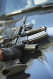 Policeman's Hand Picking Up Gun From Car Hood. Closeup of policeman's hand picking up gun from car hood Royalty Free Stock Photo