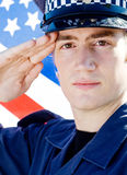 Policeman salute. Young american policeman salute, background is USA flag Royalty Free Stock Photos