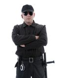 Policeman. Or security guard wearing black uniform and glasses standing confidently with folded arms, shot on white stock photography