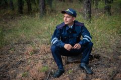 Policeman sits on the grass in the forest and thinks royalty free stock photos