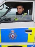 Policeman sitting in police car Stock Photo