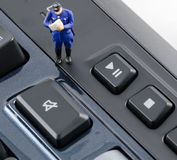 Policeman standing on the keyboard with mute botton. Miniature policeman standing on the keyboard with mute botton Royalty Free Stock Photo