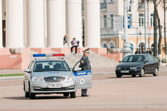 A policeman stands next to a patrol car in the background Dramat Royalty Free Stock Photos