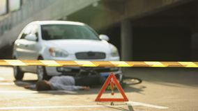 Policeman with tape fencing crime scene area, car accident with bicycle, victim. Stock footage stock video footage