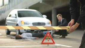 Policeman taping car accident area, male driver sitting near victim on road. Stock footage stock footage