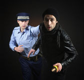 Policeman and thief. Robbery scene. Unaware officer that a crime is being comited Stock Image