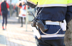 policeman in uniform with a radio transmitter and gun during a d Stock Image
