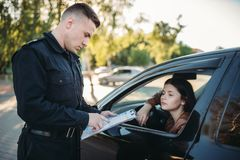 Policeman in uniform writes fine to female driver. Policeman in uniform writes a fine to female driver. Law protection, car traffic inspector, safety control job royalty free stock image