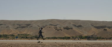 Policeman walking in Afghanistan. A member of Afghan National Police (ANP) walking alone along the road in Logar province, Afghanistan (summer 2011 Royalty Free Stock Photo