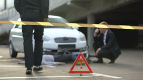Policeman walking through crime scene tape, checking car accident victim pulse. Stock footage stock video