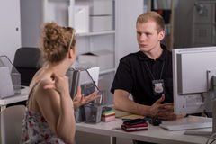 Policeman at work. Young policeman is taking testimony from woman Stock Image