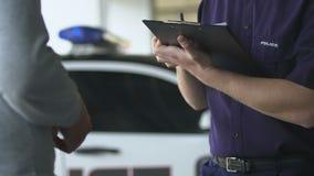 Policeman writing fine lawbreaker standing near patrolman interviewing witness