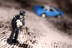 Policeman writing ticket. A miniature figure policeman writes a traffic ticket or citation. His blue patrol car is in the background with its lights on top. He Royalty Free Stock Photo