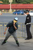 A policeman and a young man on roller skates. Beijing. China 2016. Chinese people of various professions. met in various cities. a policeman and a young man on royalty free stock photography
