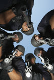 Policemen Aiming With Guns Against Sky Stock Photos