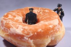 Policemen and donuts - comical. Comical shot of two miniature police figures are ready to eat a giant donut!   The doughnut is glazed with sugar Royalty Free Stock Image
