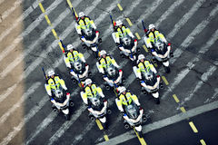 Policemen riding motorcycles Stock Photos