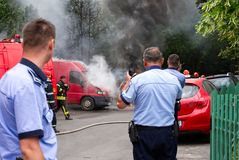 Policemen securing the area for the firemen team. Bucharest, Romania - May 07, 2018: Cars on fire blow up on the streets of Bucharest Royalty Free Stock Photos