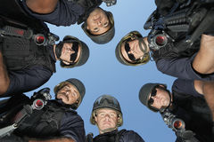 Policemen Standing Against Sky. Low angle portrait of policemen standing against sky Stock Photo