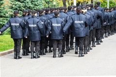 The policemen in uniform with the inscription Police in Ukrainian, goes along the street in Dnipro city Ukraine. The policemen in uniform with the inscription stock photography