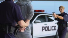 Policewoman aiming gun at criminal, male mate arresting hooligan, putting in car. Stock footage stock video