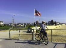 Policewoman on Bicycle. Spring Lake, NJ USA July 18, 2016 Policewoman on bicycle patrolling the boardwalk near an American flag Stock Images
