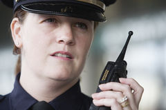 Policewoman communicating over her radio. Stock Photos