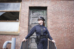 Policewoman on patrol checking urban building. Royalty Free Stock Photography