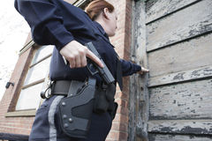 Policewoman on patrol checking urban building. Stock Photos
