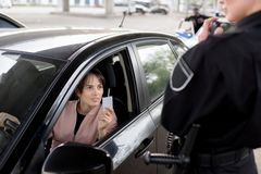 policewoman with portable radio and young woman in car holding royalty free stock photography
