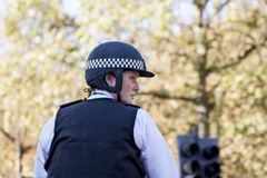 Policewoman during UK Changing of the Guards in London. Female mounted policewoman controlling traffic  in London during the changing of the guards marching Royalty Free Stock Image