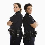 Policewomen back to back. Portrait of two mid adult Caucasian policewomen standing back to back looking over their shoulders smiling at viewer Royalty Free Stock Image