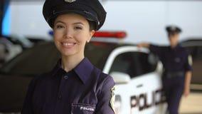 Policière asiatique de sourire posant à la caméra contre l'associé près de la voiture de patrouille, devoir banque de vidéos