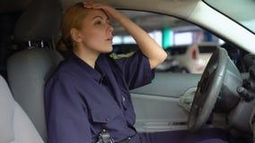 Policière fatiguée enlevant le chapeau de service se reposant dans la voiture de patrouille, poste de nuit banque de vidéos