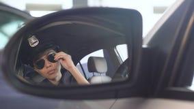 Policière sûre mettant sur des lunettes de soleil regardant dans le rétroviseur de la voiture banque de vidéos