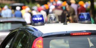 Policie as sirenes dos carros-patrulha que piscam durante a demonstração de Imagem de Stock