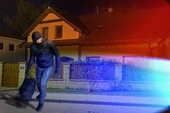 Policie luzes e o assaltante mascarado fugitivo com passa-montanhas e blac Imagem de Stock