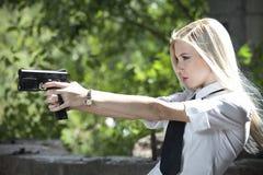 Policie a mulher que aponta com o revólver na blusa e amarre-a fotografia de stock royalty free