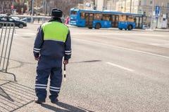 Policie o regulador em uma estrada ocupada em um uniforme Foto de Stock