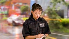 Policier américain asiatique à la scène du crime prenant des notes Photographie stock