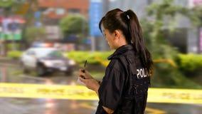 Policier américain asiatique de femme à la scène du crime, vue de côté, Photos libres de droits
