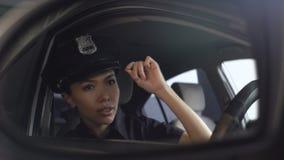 Policier asiatique ajustant son chapeau uniforme regardant dans le rétroviseur banque de vidéos