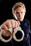 Policier avec des menottes portant des criminels à la prison Image stock