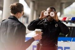 policier d'afro-américain feignant des beignets en tant que ses yeux pour amuser image stock