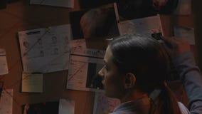 Policier féminin recherchant des idées de crime de solution sur le conseil d'enquête banque de vidéos